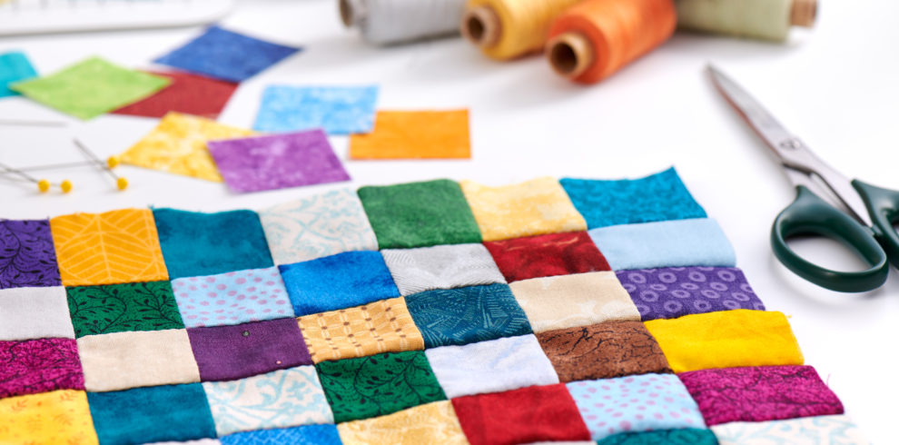 Colorful Part Of Quilt Sewn From Square Pieces, Spools Of Thread