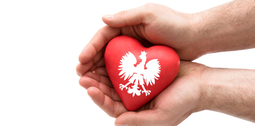 Hands covering Polish coat of arms on a red heart isolated on wh